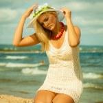 Beautiful blonde girl in hat on beach, summertime — Stock Photo #52413127