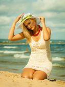 Beautiful blonde girl in hat on beach, summertime — Stock Photo