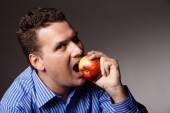 Diet nutrition. Happy man biting apple fruit — Stock Photo