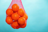 Fresh oranges fruits in mesh from supermarket — Stock Photo