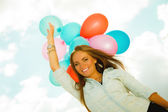 Happy girl with colorful balloons outdoors — Stock Photo