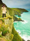Irish atlantic coast. Woman tourist standing on rock cliff — Foto de Stock