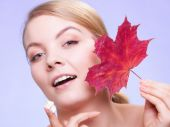 Skin care. Face of young woman girl with red maple leaf. — Stock Photo