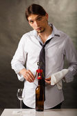 Man opening bottle of wine with corkscrew — Stock Photo