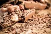 Chocolate shavings and pieces on wooden table — Stock Photo