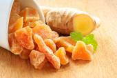 Closeup root and candied ginger on wooden table — Stock Photo