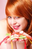 Redhair girl holding sweet food jelly candy on pink. — Stock Photo