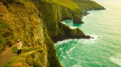 Irish atlantic coast. Woman tourist standing on rock cliff — ストック写真