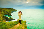 Irish atlantic coast. Woman tourist standing on rock cliff — Stock Photo