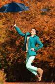 Girl jumping with blue umbrella in autumnal park — Stock Photo
