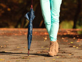 Girl walking with umbrella in autumnal park — Stockfoto