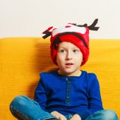 Little boy in red winter reindeer hat at home — Stock fotografie