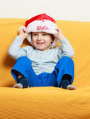Little boy in red santa hat sitting on couch at home — Stock Photo