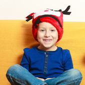 Little boy in red winter reindeer hat at home — 图库照片