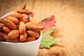 Almonds in bowl on wooden background — Stok fotoğraf