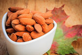 Almonds in bowl on autumnal background — Stok fotoğraf