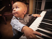 Boy child kid playing on digital keyboard piano synthesizer — Стоковое фото