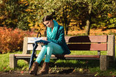 Girl relaxing in autumnal park reading book. Fall. — 图库照片