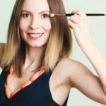Woman applying eyeshadow with makeup brush — Stock Photo #53265543
