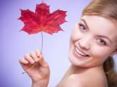 Young woman with maple leaf — Stock Photo