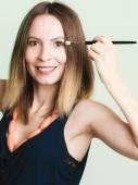 Woman applying eyeshadow with makeup brush — Stock Photo