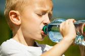 Boy drink water from bottle — Stock Photo