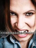 Angry woman biting metal chain — Stock Photo