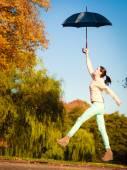 Girl jumping with umbrella — Stock Photo