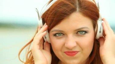 Kvinna på stranden lyssna på musik — Stockvideo
