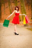 Autumn shopper woman with sale bags outdoor in park — Стоковое фото