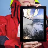 Sailor showing yacht boat on tablet — Stock Photo