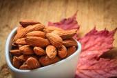 Almonds in bowl on autumnal background — Photo