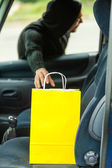 Thief stealing shopping bag from car — Stock Photo
