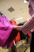 Woman choose blouse at shop — Stock Photo
