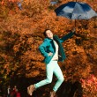 Girl jumping with umbrella in park — Stock Photo #54936083