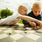Children playing checkers board game — Stock Photo