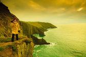 Woman tourist on rock cliff — Stock Photo