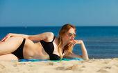 Girl in bikini sunbathing on beach — Stock Photo