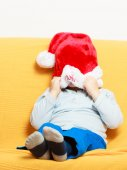 Boy in santa hat on couch — Stock Photo