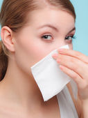 Sick woman sneezing in tissue — Stock Photo