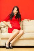 Kobieta w ciąży na kanapie — Zdjęcie stockowe