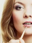 Woman applying lipstick with brush — Stock Photo