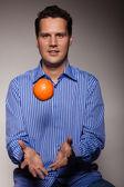 Man throwing orange — Stock Photo