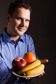 Happy young man holding fruits — Stock Photo