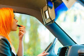 Girl doing makeup while driving car — Stok fotoğraf