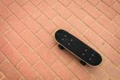 Skateboard deck on red paving stone — Stock Photo