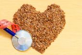 Flax seeds heart shaped and stethoscope — Stock Photo