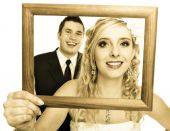 Bride and groom in wooden frame — Stock Photo