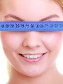 Woman covering eyes with measuring tape — Stock Photo