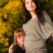 Pregnant woman with daughter in park — Stock Photo #56507881